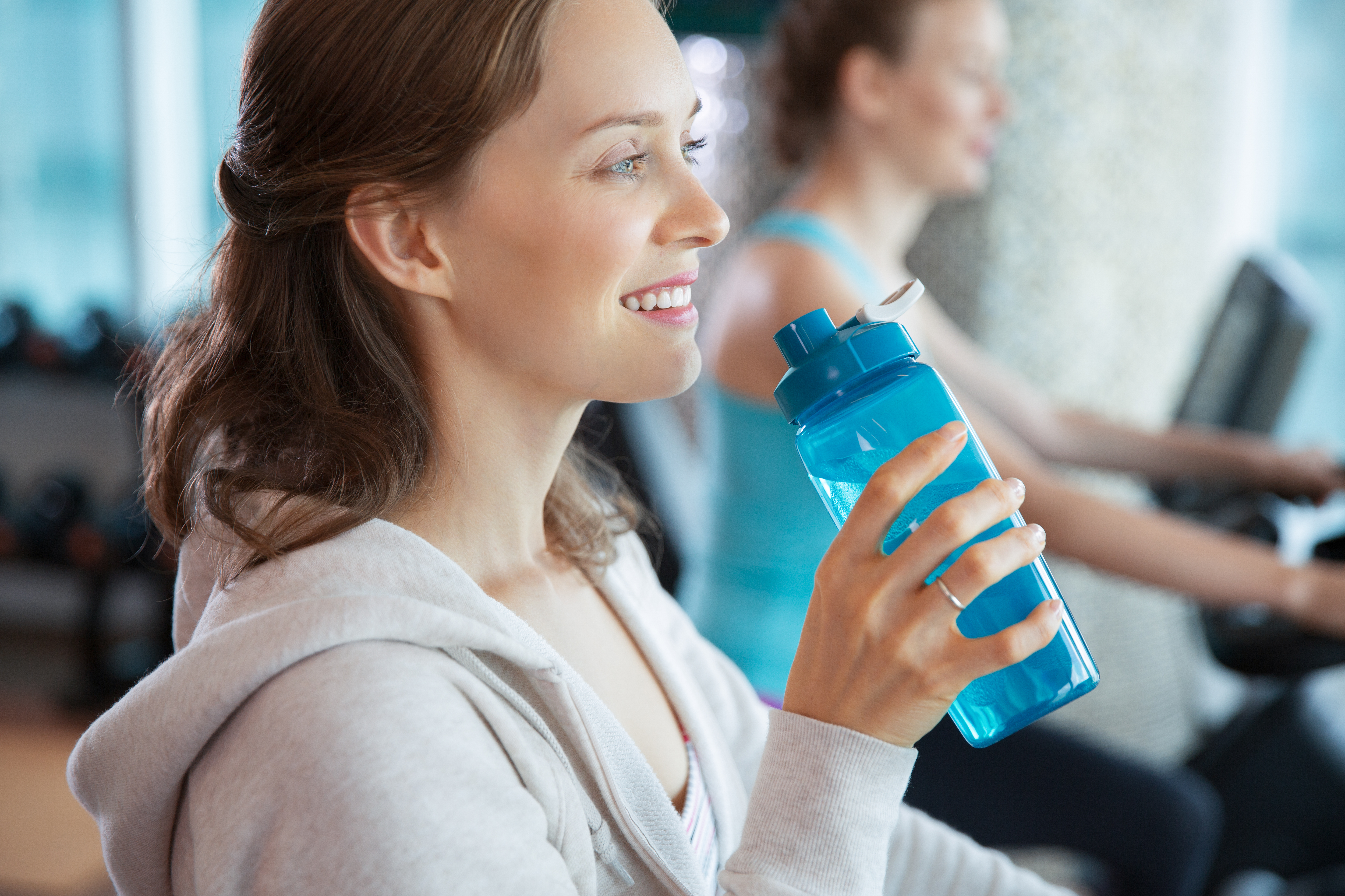 Smiling young Caucasian woman drinking water while training on exercise bike in modern gym. Woman riding spinning bike in background
